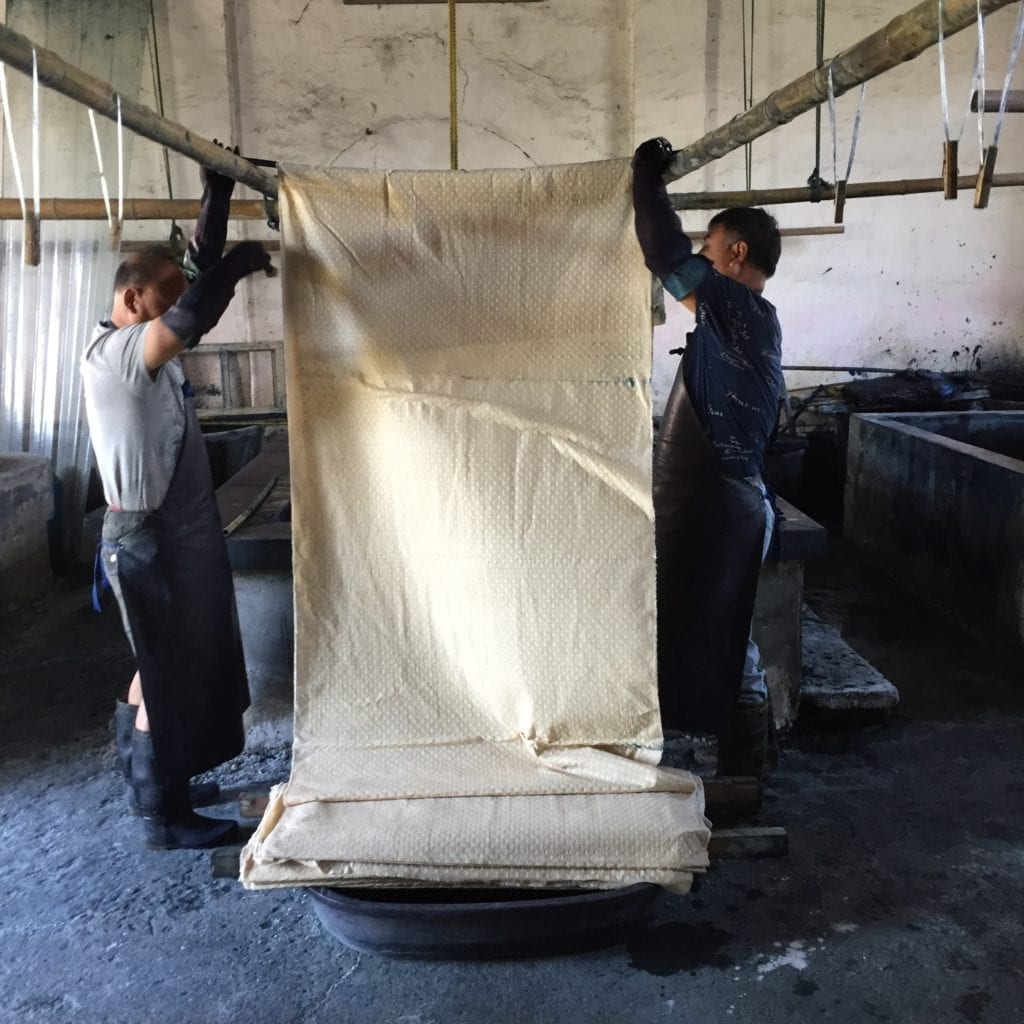 The calico is prepared for the first dip in the indigo vat.