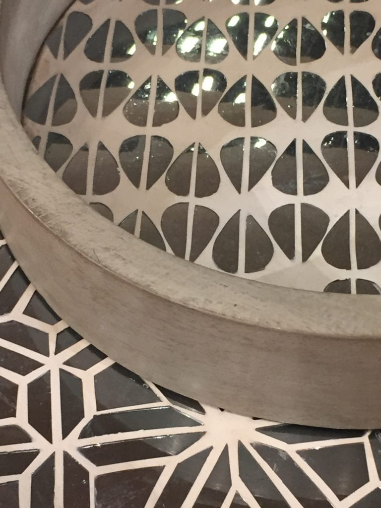A mirror-mosaic and plaster circular tray against mirror mosaic furniture, both handmade in India.