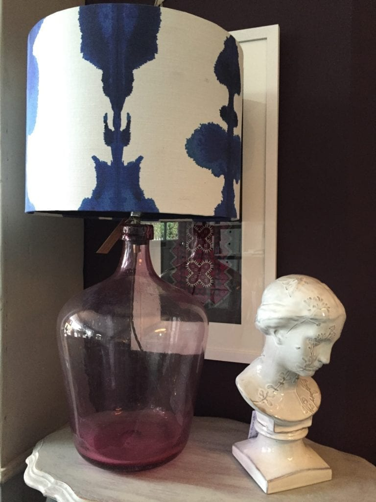 An indigo blue 'Inkat' fabric by Korla on a drum shade teamed with a pink Pooky Lights glass lamp base sat on a painted oval side table next to a white ceramic bust.