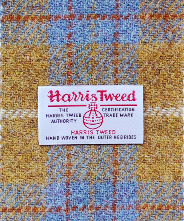 A close-up shot of the Harris Tweed Authority orb label of authenticity against a grey and mustard drum shade.