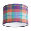 A cut out image of a Harris tweed check drum shade in zingy purple, orange, pale blue and turquoise from Telescope Style.
