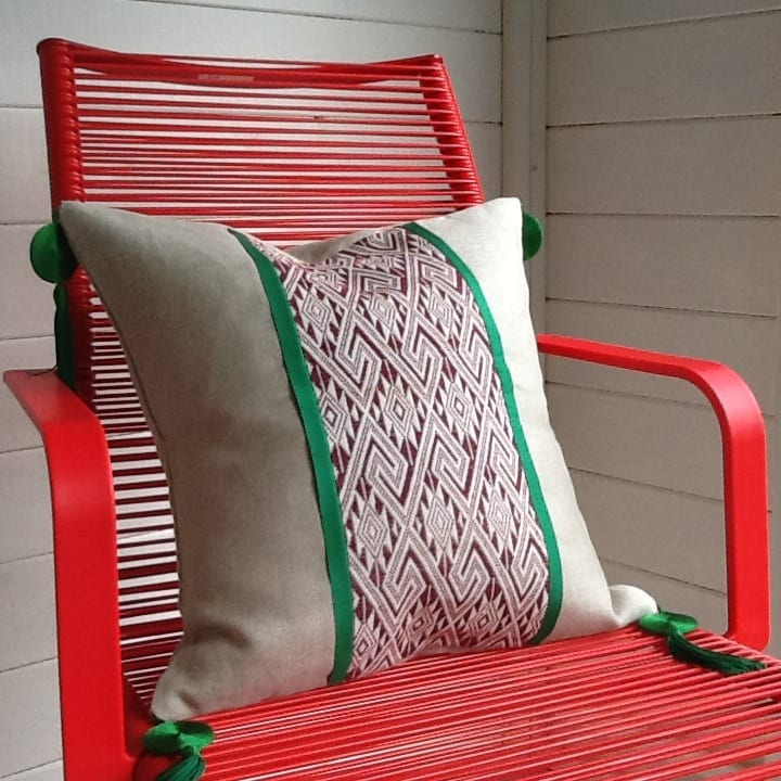 A modern, pillar box red, wire chair with a tasselled natural linen cushion in chocolate Thai textile with green silk trim.