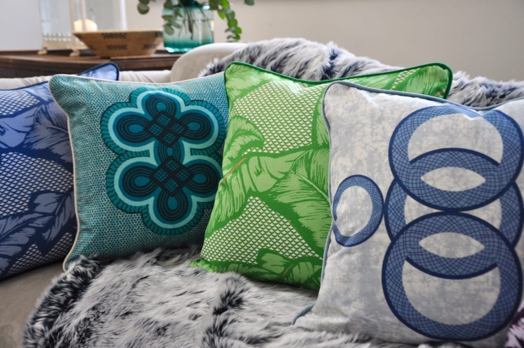 A vibrant selection of aqua, blue and green African-inspired cushions arranged on a grey, faux fur throw on a sofa.
