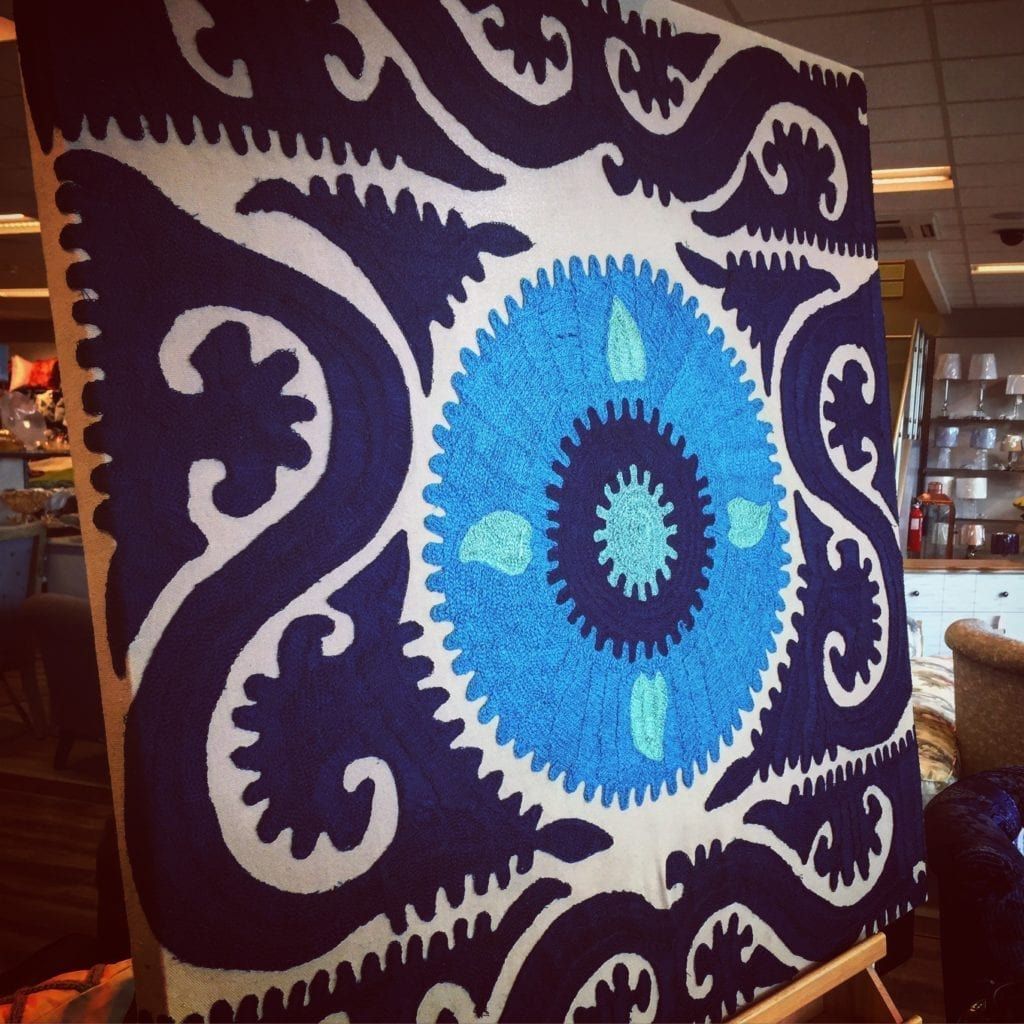 A shot of a blue, crewel-work, ethnic textile as canvas wall art.