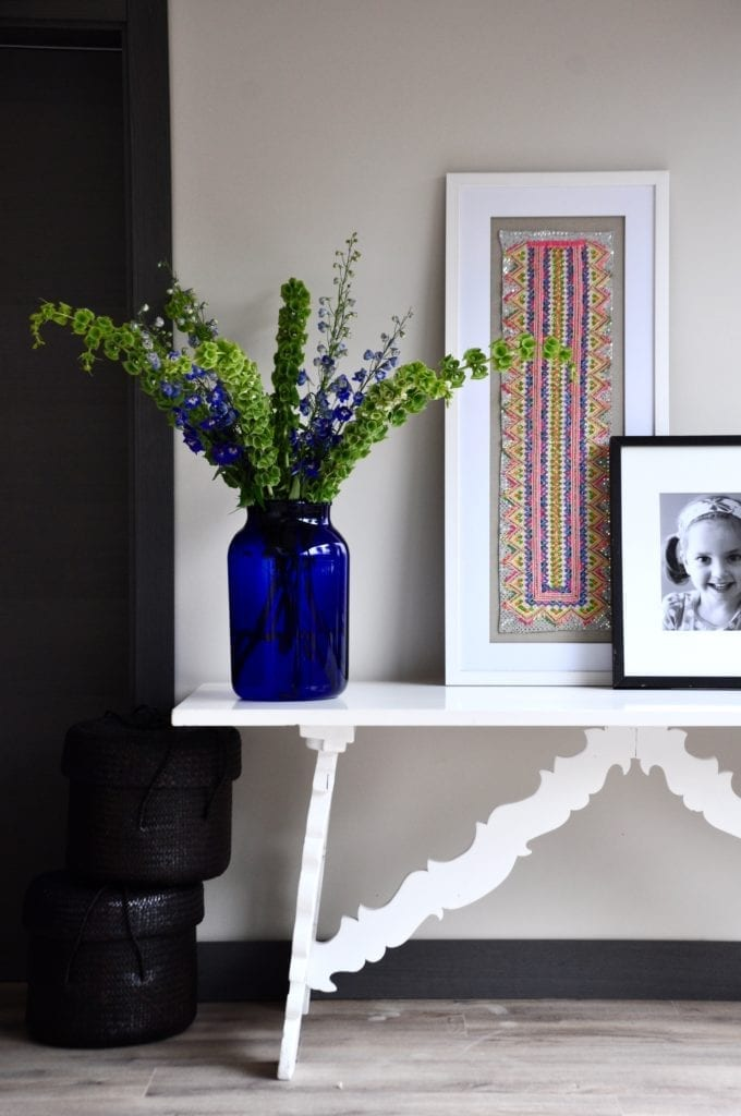 A neon 'colour pop' Thai framed textile displayed on a white painted side table with a large blue glass vase of Bells of Ireland and Delphiniums.