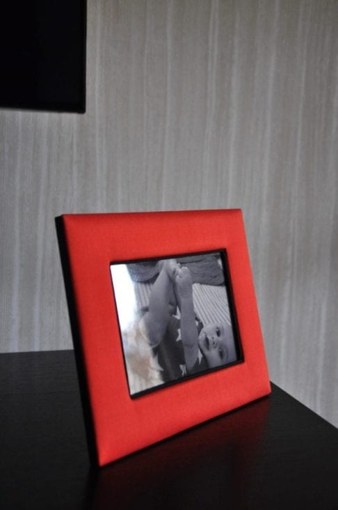 A Thai-silk, red, photograph frame with a picture of a baby against a pale, strié-wallpapered backdrop.