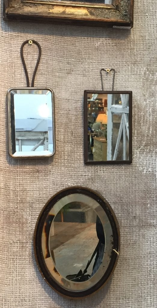 A collection of small vintage mirrors displayed on a hessian-clad wall.