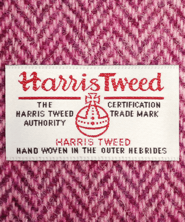 Close-up shot of Harris tweed orb label on pink herringbone tweed.