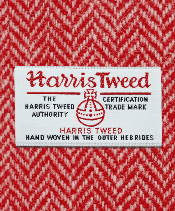 Close-up shot of Harris tweed orb label on red herringbone tweed.