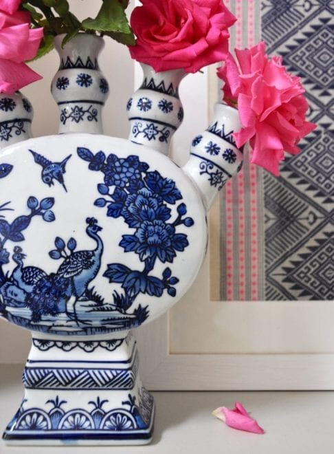 Detail of a Dutch-inspired blue and white painted tulip vase filled with pink roses on a ledge with a framed Thai textile behind.