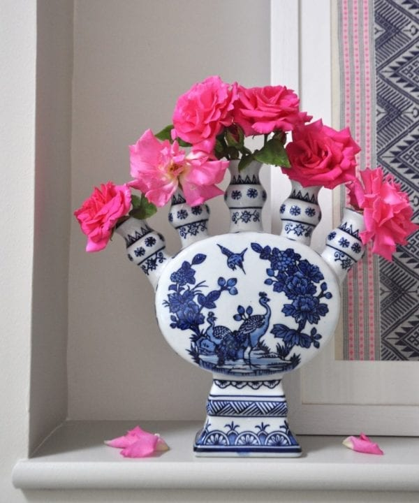 Front on shot of a Dutch-inspired blue and white painted tulip vase filled with pink roses on a ledge with a framed Thai textile behind.