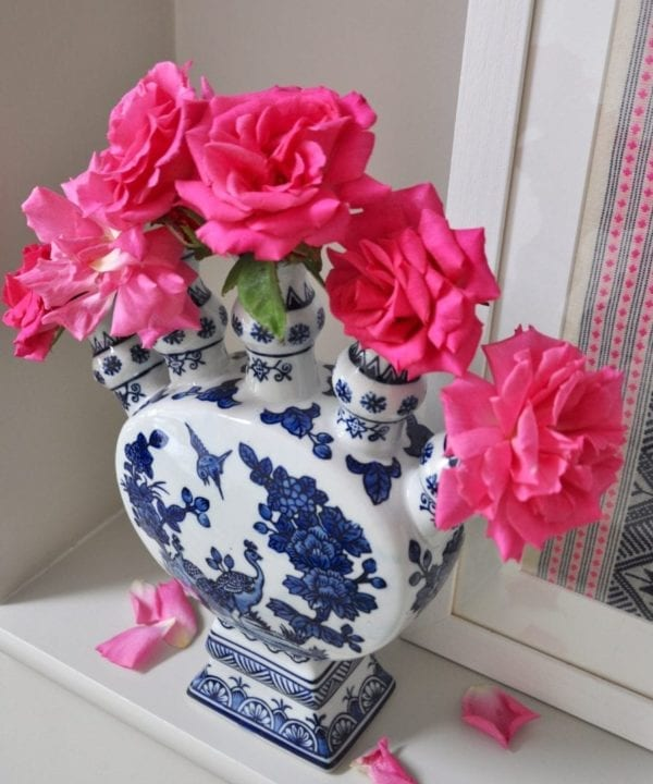 An overhead shot of a Dutch-inspired blue and white painted tulip vase filled with pink roses on a shelf.