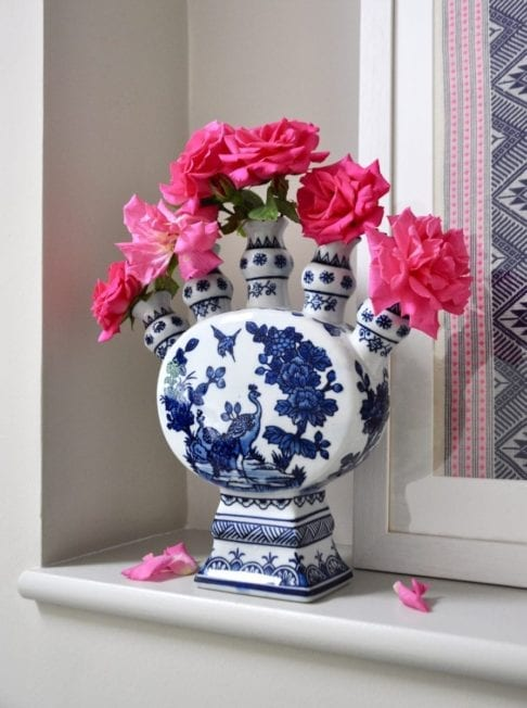 A Dutch-inspired blue and white painted tulip vase filled with pink roses on a ledge with a framed Thai textile behind.