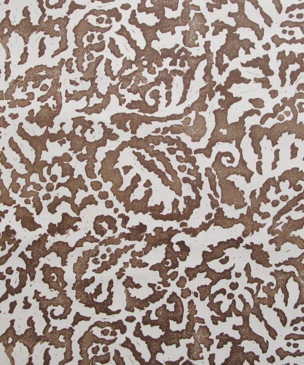 A close up of the Majolica, Italian inspired brown patterned wallpaper in earthy-hued Gaucho with a pale, off-white ground.