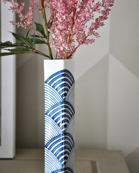 A close up shot of a hand-painted, blue and white Japanese bud vase with 'tranquility' waves design.