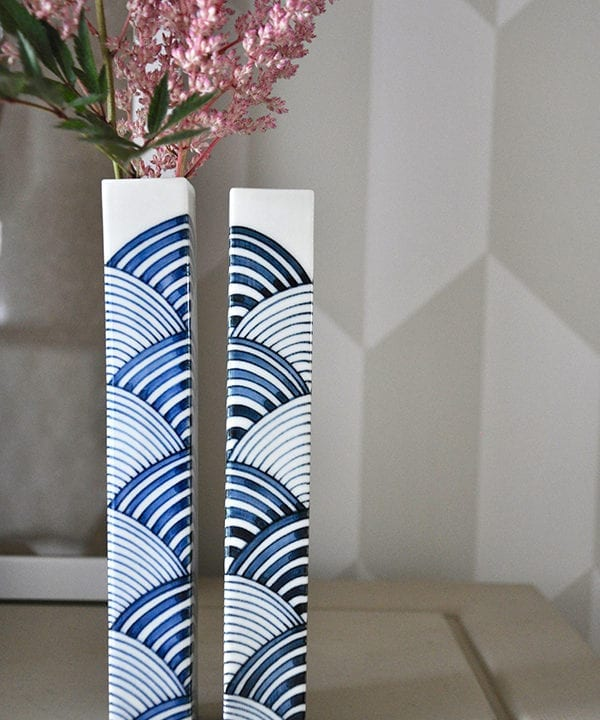 Close up shot of two hand-painted, Japanese bud vases in cobalt and indigo blues.