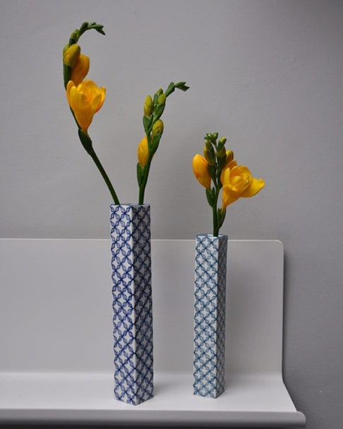 Hand-painted , lattice-patterned Japanese bud vases holding yellow freesias on a shelf.