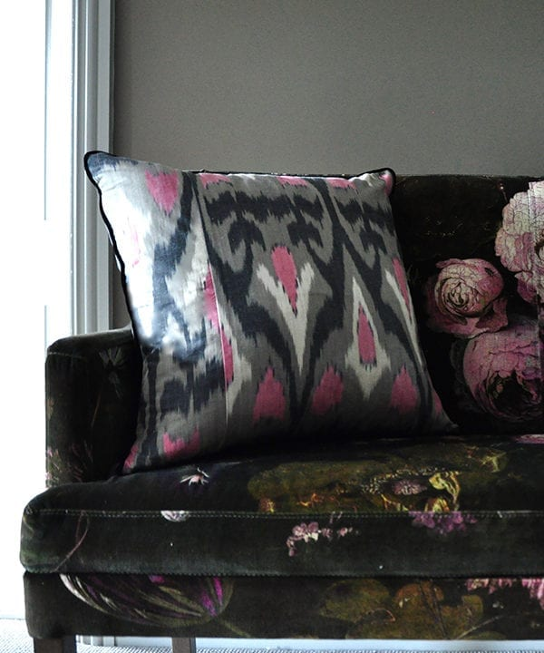 A vertically arranged, square, pink and warm, grey, silk ikat cushion with black accents sat on a floral velvet upholstered banquette.