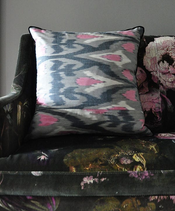 A horizontally-arranged, square, pink and warm, grey, silk ikat cushion with black accents sat on a floral velvet upholstered banquette.