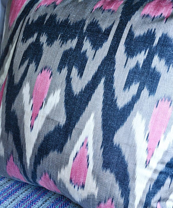 Detail of a pink and warm, grey, silk ikat cushion with black accents.