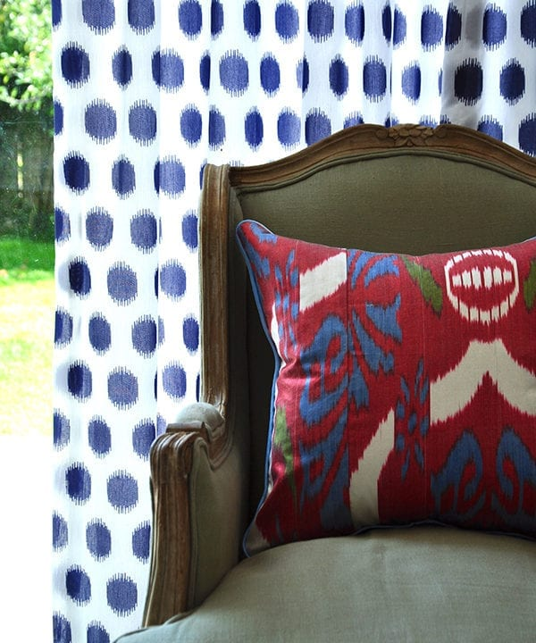 A colourful red, silk, ikat cushion on a French wing chair againstb a blue and white curtain with a view to the garden.