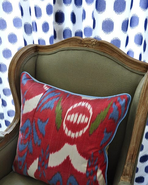 A vibrant, red, ikat cushion on a French style wing chair with blue and white polka dot curtain in the background.