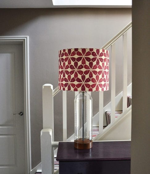Cranberry red lampshade in 'Maroc' on a landing side table,Telescope Style.
