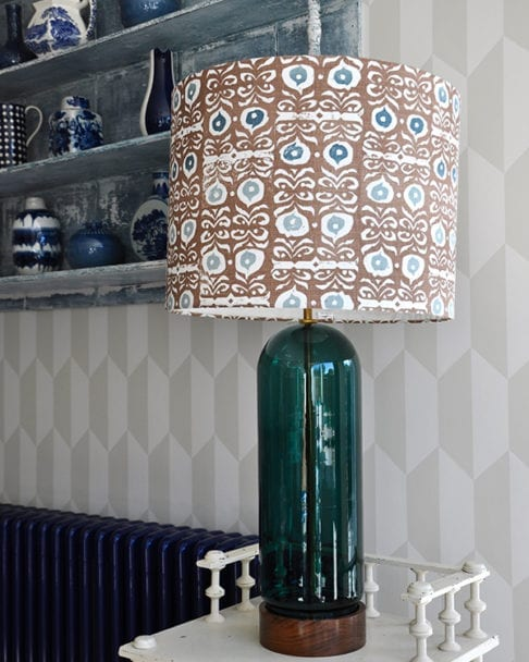 A statuesque patterned lampshade on a cream side table in front of geometric wallpaper.