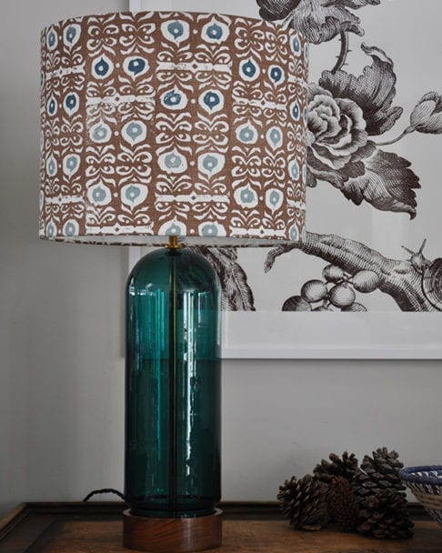 A patterned lampshade in teal blues and brown with a teal glass lampbase.