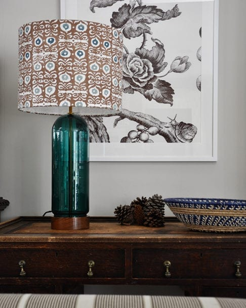 A teal blue and brown patterned lampshade on a wooden sideboard with a floral print in the background.
