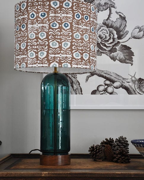 A patterned lampshade in teal blues and brown on a teal glass and wood base.