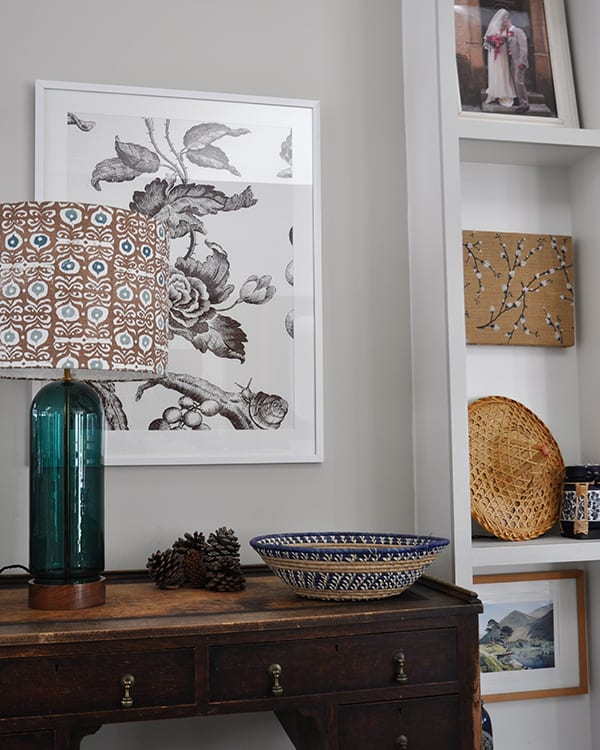 Shallow, built-in shelving next a wooden desk with a framed floral print above and a patterned lampshade on a teal glass base.