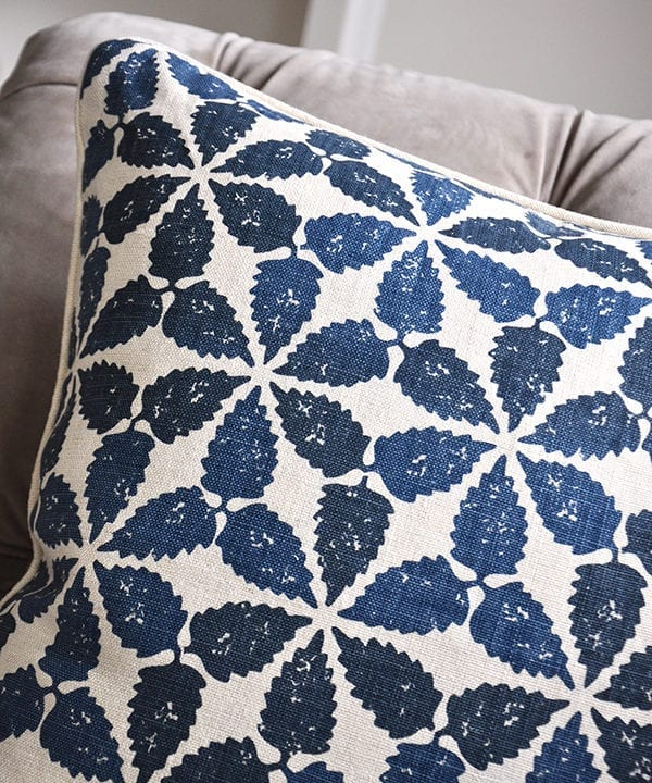 A close up shot of an indigo blue, hand-printed linen cushion with a Moroccan-inspired design.