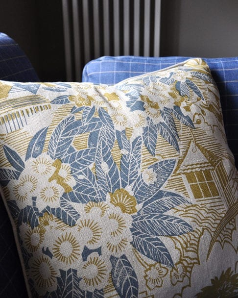 A close-up shot of Webb's Wonder hand-printed linen cushion in chartreuse on a blue check sofa available through Telescope Style.