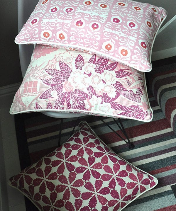 A trio of pink and raspberry cushions: Iznik, Webb's Wonder pink floral cushion and Maroc on a chair and stripy carpet. Available from Telescope Style.