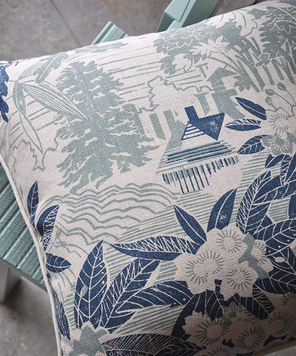A pale blue floral cushion depicting an Arts & Crafts house in it's garden setting photographed on a pale turquoise chair.