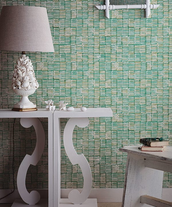 Japanese wallpaper in a verdant, green colourway styled with a white console and sculptural, ceramic lamp.