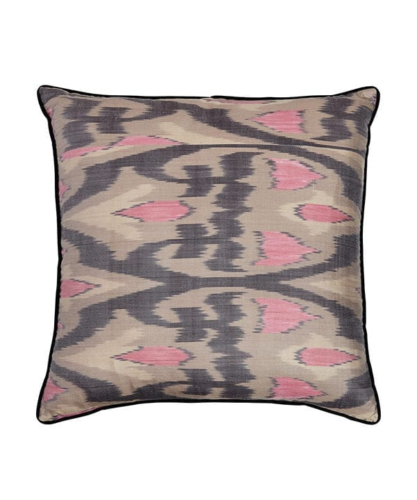A cut out shot of pink, black and warm grey ikat cushions.