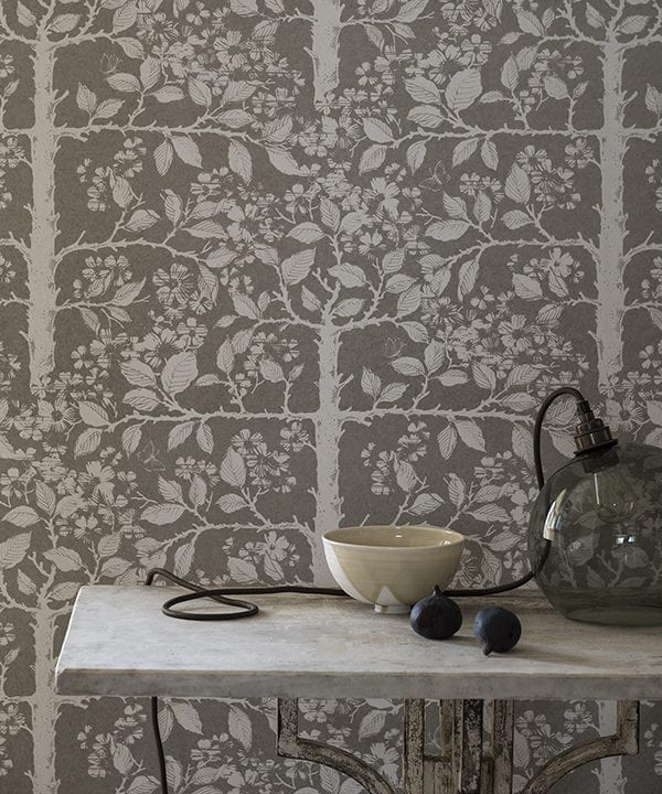 Grey botanical wallpaper in a chic neutral hue depicts espaliered trees redolent of walled gardens in English country houses.