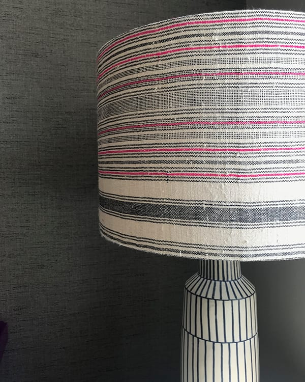 Black and white lampshade closeup shot, with a pink stripe running through it in a slubby, vintage, Thai, handwoven hemp fabric. Showcases eclectic interior design style.