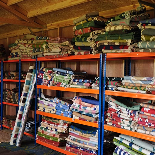 Rows of shelving piled up with colourful dhurrie rug designs available from Mahout Lifestyle at their north Oxfordshire base.