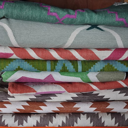 Stacked Indian dhurrie rugs at the Mahout Lifestyle's 'show shed' in north Oxfordshire.
