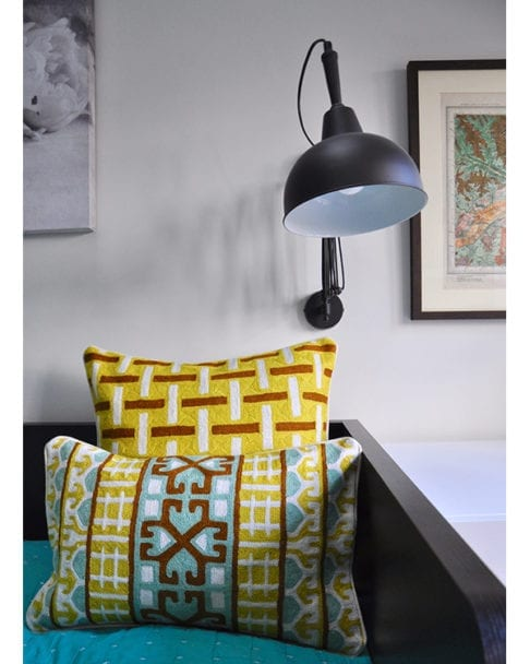 Crewel work cushion covers in turquoise and chocolate with a yellow geometric background, from Telescope Style.