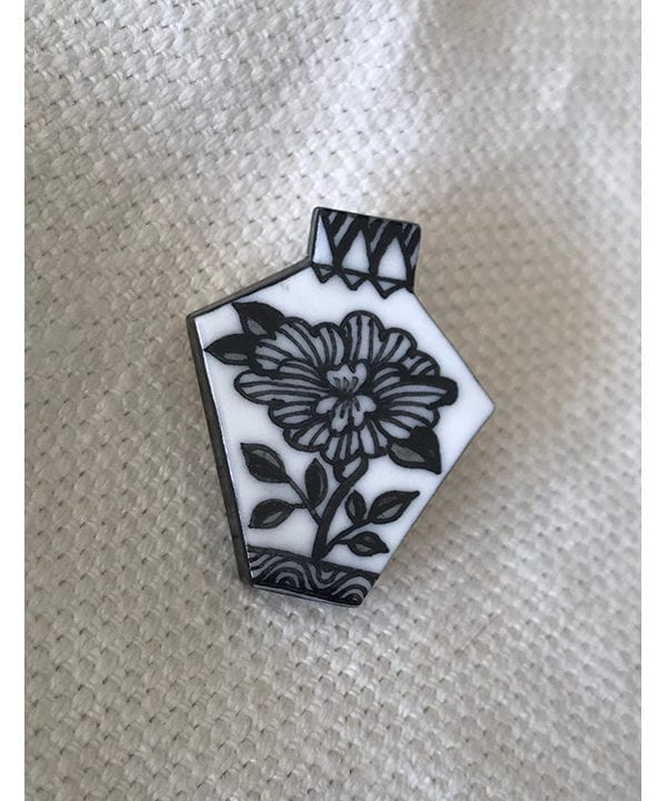 A hand-painted Japanese floral art black and white brooch displayed on cream linen.