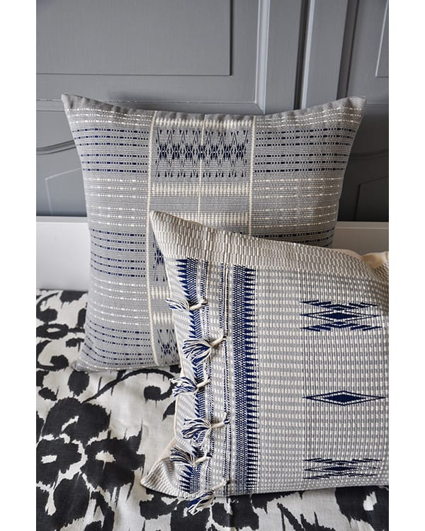 Tasselled blue grey cushion covers handmade in Nagaland, India against grey panelling.
