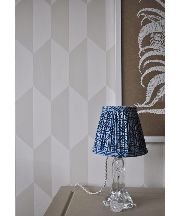 A petite block-print lampshade with a geometric grid design and geometric wallpaper behind.