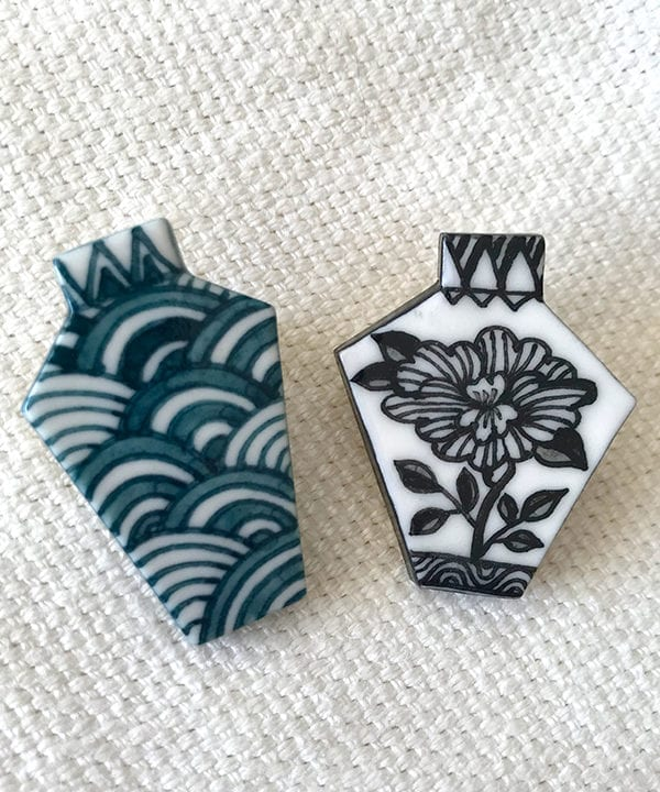 Two porcelain Japanese jewellery brooches depicting a monochrome floral design and a repeating Japanese waves motif - a symbol of tranquility.