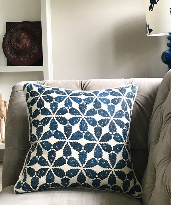 An indigo patterned cushion with a Moroccan motif on a grey, velvet Chesterfield sofa.