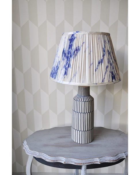 Indigo blue gathered silk lampshades in Japanese-style Shibori silk. The lampshade is sat on a painted, grey, side table with geometric wallpaper behind.