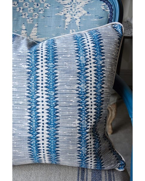 Detail of a hand-printed, linen, blue striped cushion in a tribal design.